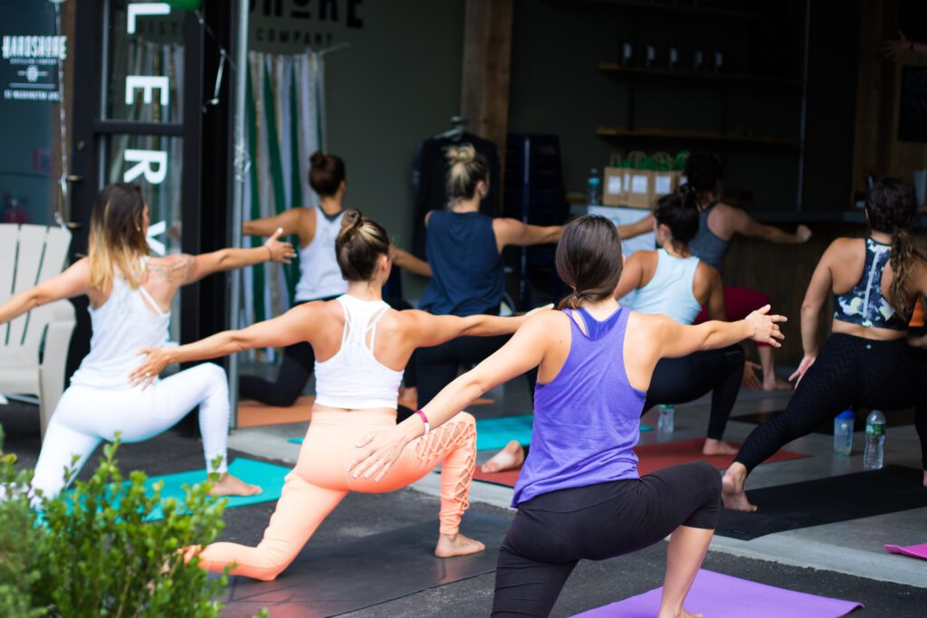 woman in white tank top and pink leggings doing yoga